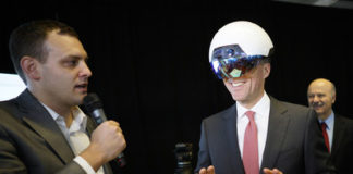 Ben Holfeld of Accenture's AI practice, left, helps Canadian Finance Minister Bill Morneau, right, use a DAQRI Smart Helmet during the launch of the Vector Institute for AI at the MaRs Discovery District in Toronto, Ont. on Thursday, March 30, 2017