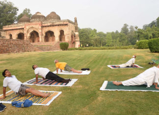 People perform Yoga, on the occasion of the 7th International Day of Yoga 2021, at Lodhi Garden, in New Delhi on June 21, 2021.